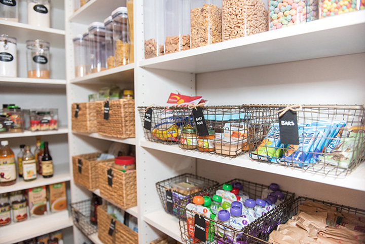 Pantry shelves organized with baskets, plastic containers, and jars