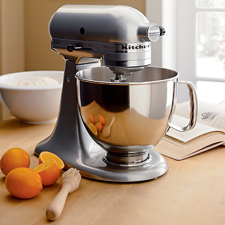 Silver kitchenaid mixer on wood surface, oranges, white mixing bowl