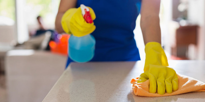 Woman's hand in yellow dish glove using orange microfiber clothe on counter